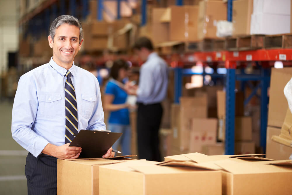 man standing by boxes in a warehouse